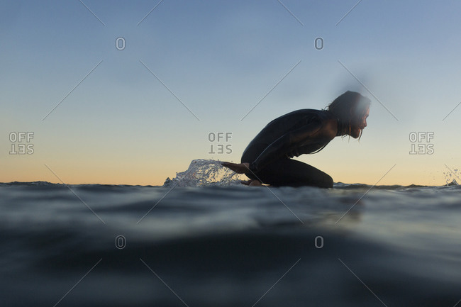 Side view of confident man surfing on sea during sunset