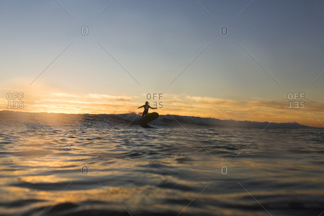 Distant view of silhouette woman surfing on sea during sunset