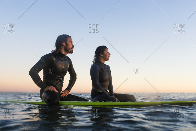 Thoughtful young couple relaxing on surfboards in sea during sunset