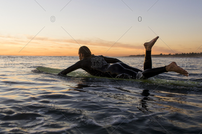 Side view of man lying on surfboard in sea during sunset