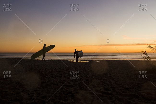 Couple carrying surfboards while walking on San Onofre State Beach during sunset