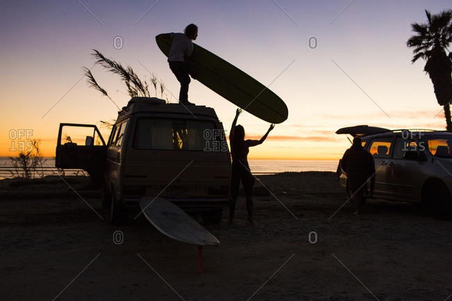 Silhouette man passing surfboard to woman while standing on mini van at San Onofre State Beach