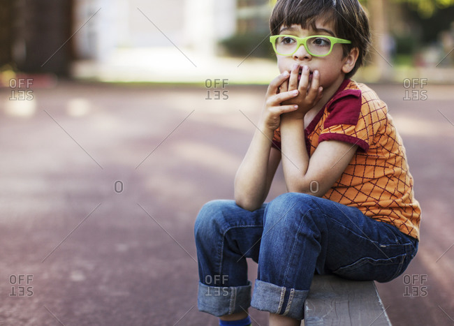 Thoughtful boy sitting on retaining wall by footpath