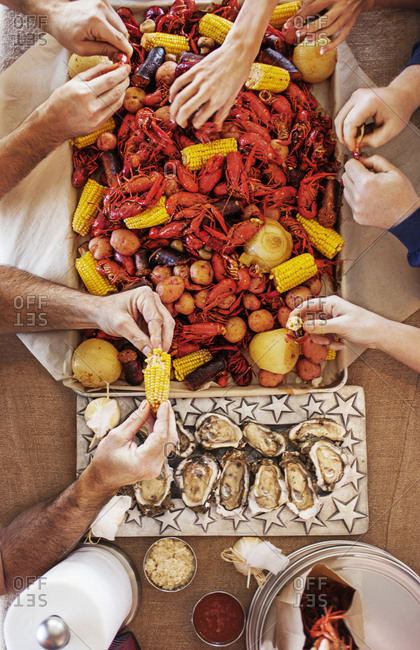 Overhead view of people eating crayfishes with potatoes, corns and oysters at dining table