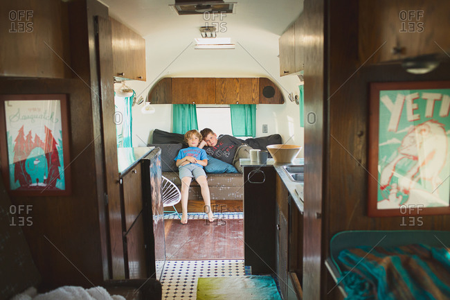 Two boys relaxing on a couch in the back of a travel trailer
