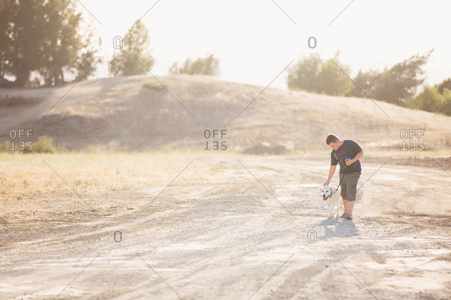 Young man petting his dog while out for a walk