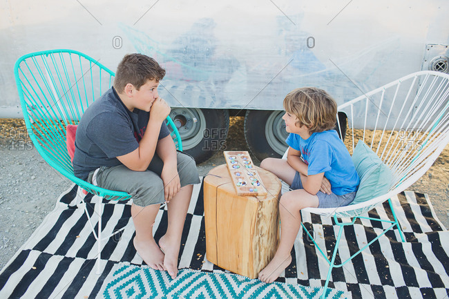 Two boys playing a game while sitting outside of a travel trailer