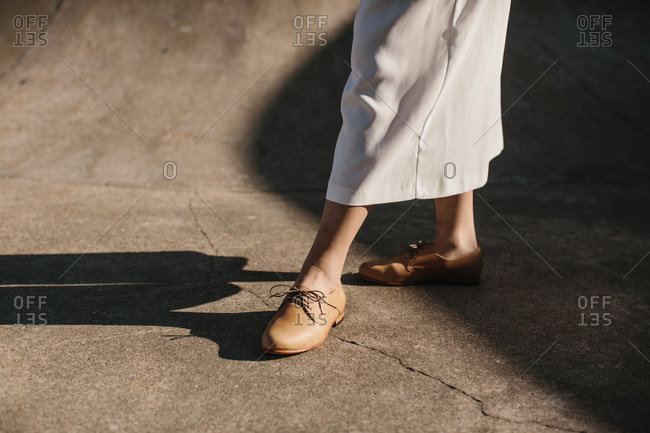 Shoes of a young woman in white pants with brown shoes