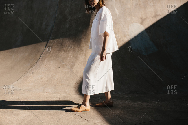 Young woman in oversized white clothing walking in a concrete bowl