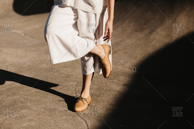 Young woman in white clothes and brown shoes reaching for her foot