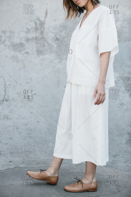 Young woman in baggy white clothing and brown leather shoes