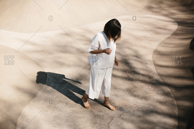 Woman in a baggy white outfit standing in a cement bowl