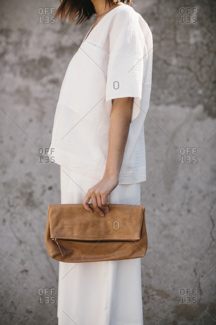 Young woman in a baggy white outfit holding a brown leather clutch