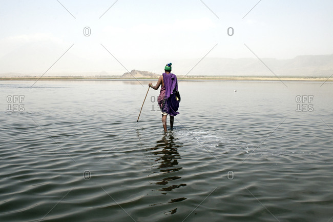 Back view of African person wading in water with stick