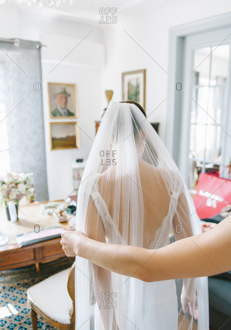 Bride getting assistance with her veil during wedding preparations