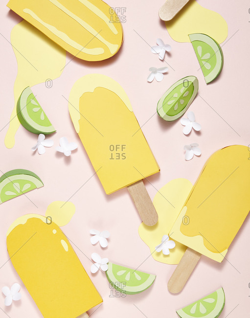 Yellow popsicles with limes and flowers on pink background