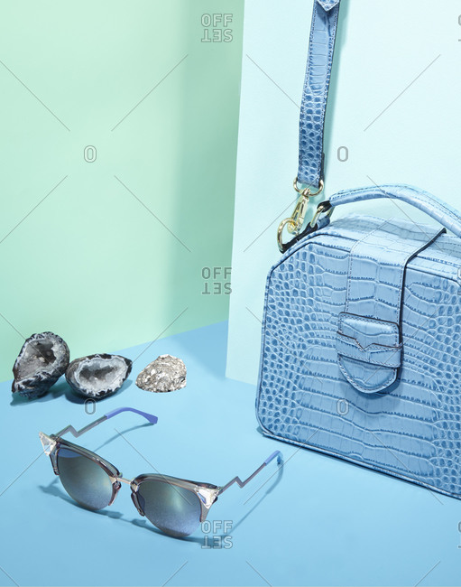 Sunglasses with reptile skin bag on blue background