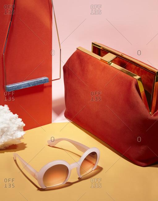 Red hinged handbag and pair of sunglasses