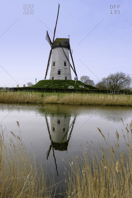 Windmill reflected in the water in Bruges, Belgium