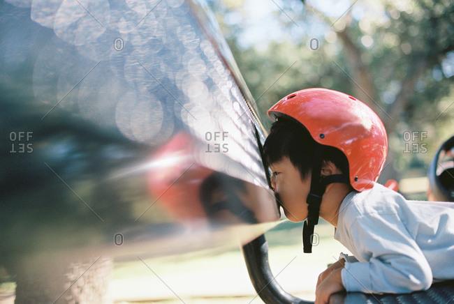 Boy in helmet lying on vehicle