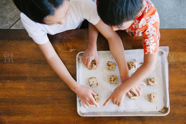 Boys placing cookie dough on tray