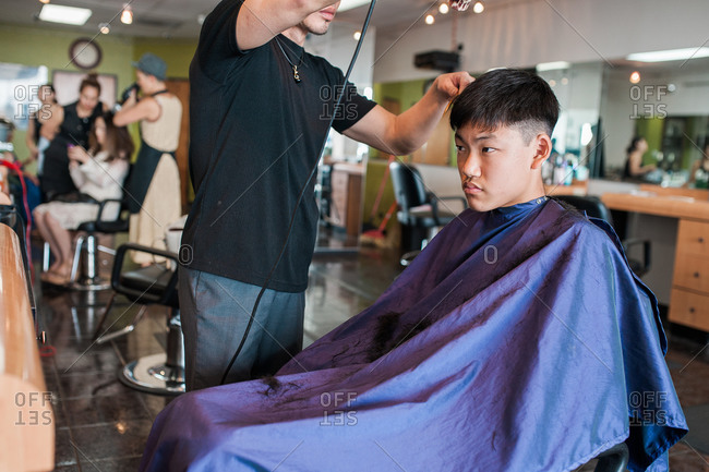 Asian teen getting a haircut