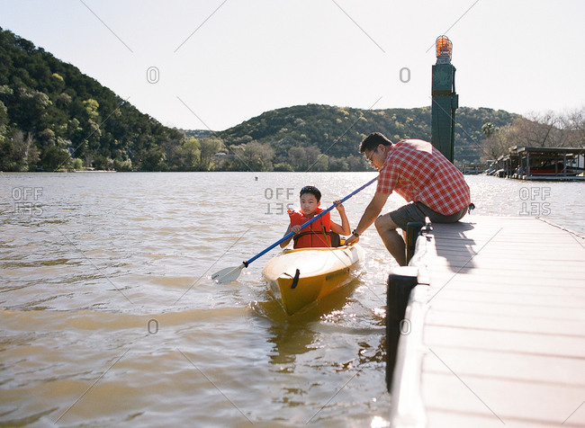 Boy preparing to go kayaking in a lake while his dad holds the boat from the dock