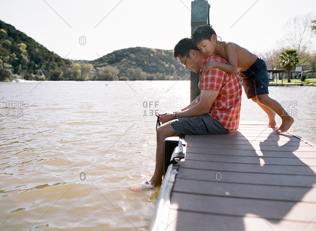Boy leaning on his dad's shoulders on a dock at a lake