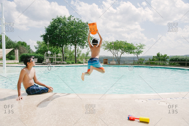 Boy jumping into a swimming pool while another teen looks on