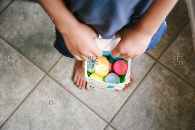 Overhead view of a child holding a basket of Easter eggs