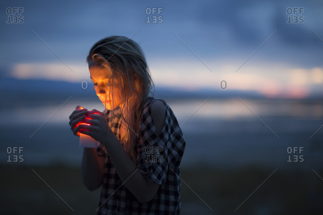 A young woman with a candle stands in the desert