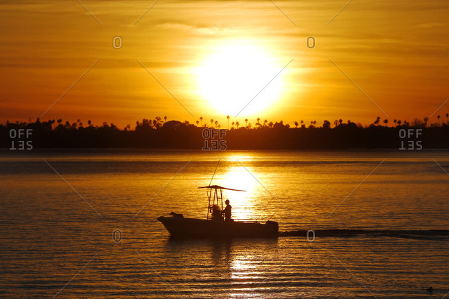 A fishing boat returns to a dock at sunset in Mission Bay in San Diego, CA