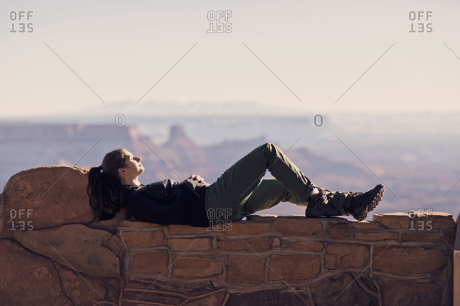 A young woman naps on a rock wall in Dead Horse State Park, Utah