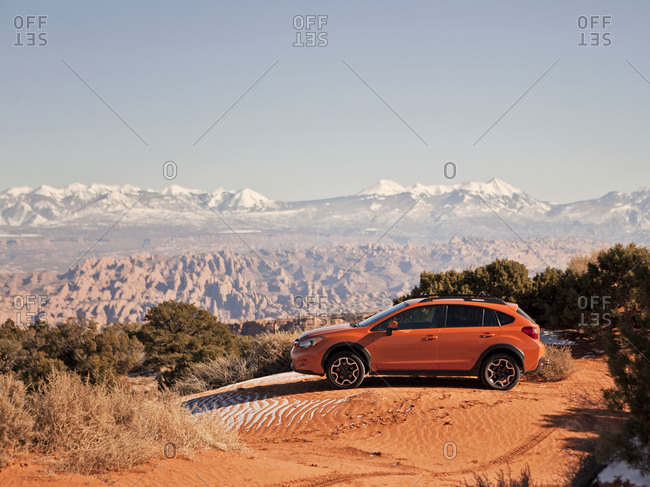 Moab, UT, USA - December 2, 2015: An orange car sits parked on a sand dune with the desert stretching out behind