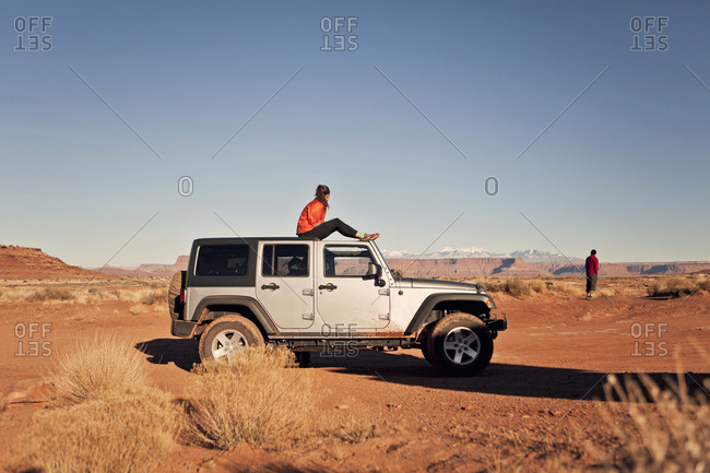 Moab, UT, USA - December 6, 2015: Two travelers take in the view from their Jeep while off roading