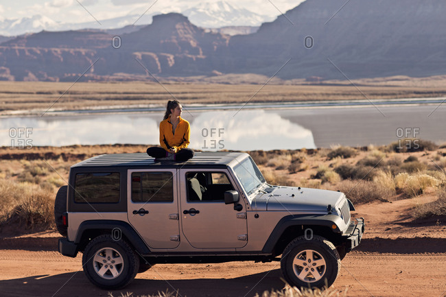 Moab, UT, USA - December 5, 2015: A young woman takes in the view of the desert from the top of her Jeep, on the White Rim Trail