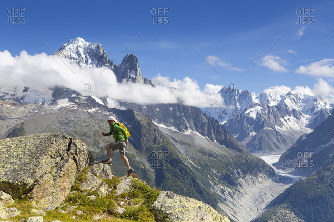 A male runner is sprinting up a steep trail in the mountains of outdoor paradise Chamonix in the French Alps
