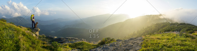 A panorama of a woman and her dog watching the sunset on Grassy Ridge