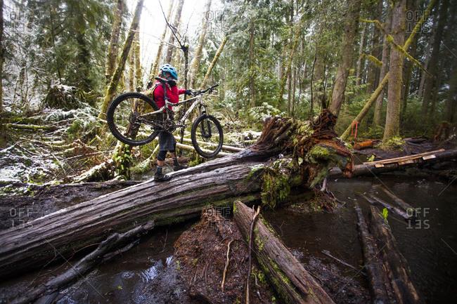 A woman carrying her mountain bike through the woody terrain of Issaquah, Washington