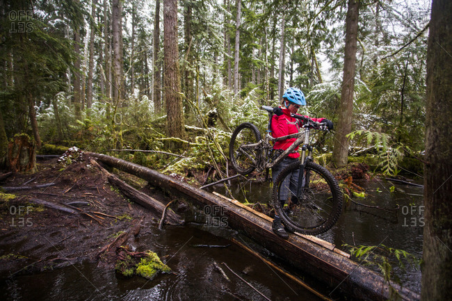 A woman carrying her mountain bike over a log