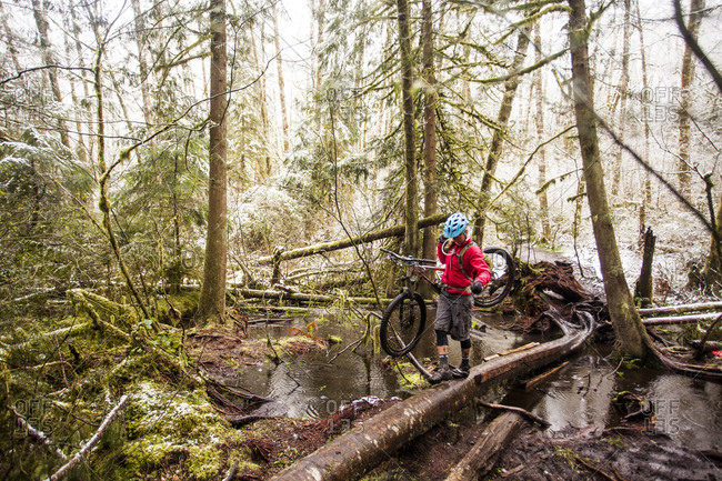 A woman carrying her mountain bike over a forest stream on a rainy day