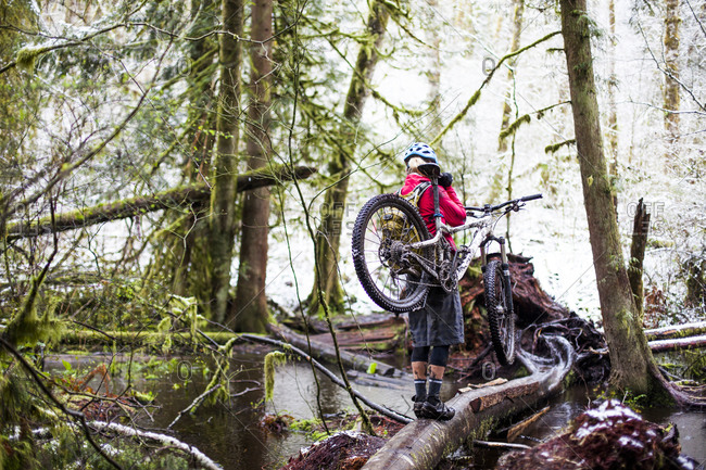 A woman carrying her mountain bike over a forest stream of Issaquah, Washington