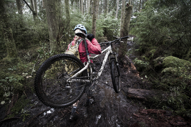 A woman carrying her mountain bike over a muddy forest