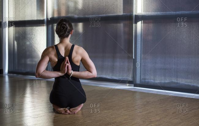 Female Yoga Instructor in Reverse Prayer in the yoga studio in Baltimore, MD