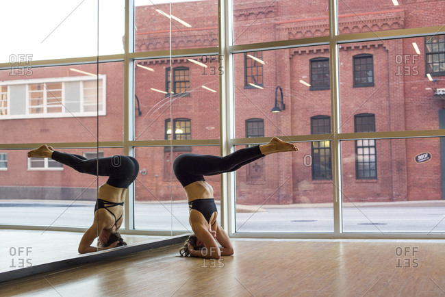 Female Yoga Instructor in head stand with pike legs in the yoga studio in Baltimore, Maryland