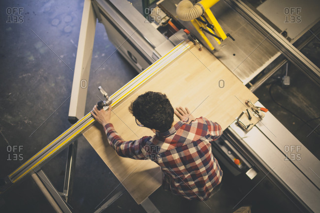 A carpenter adjusts the clamps on a sliding table saw while cutting a table top in his shop