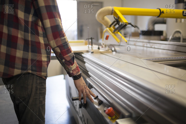A carpenter presses a button to start up a sliding table saw while working in his shop