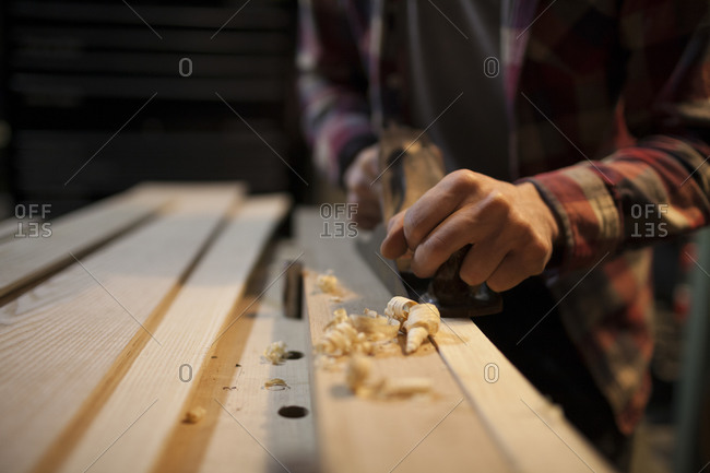 Curled wood shavings are created as a carpenter uses a hand planer to work on a piece of wood