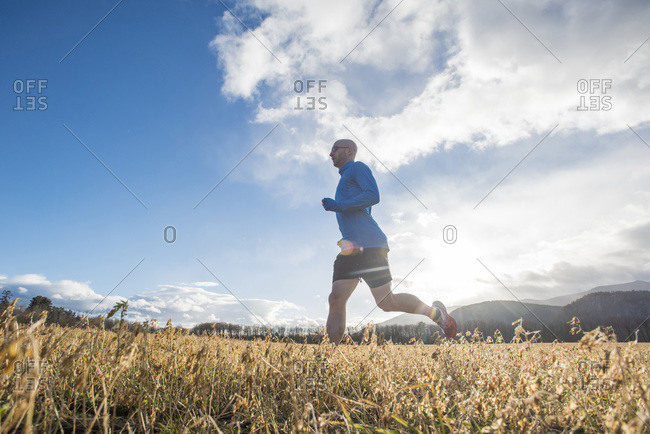 Cunchine peaking through the clouds as runner goes through a field