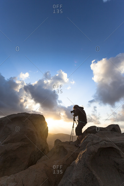Man taking photo of the sunset with tripod from the top of a mountain Fuerteventura, Canary Islands